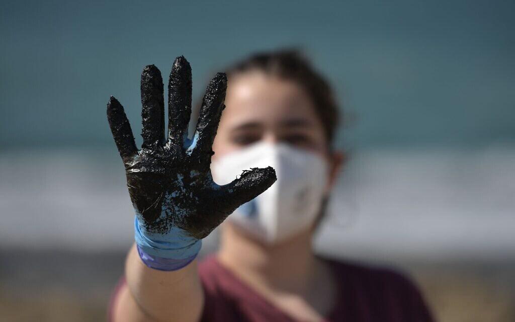 נערה מנקה זפת בחוף הבונים, 25 בפברואר 2021 (צילום: קובי גדעון לע״מ)