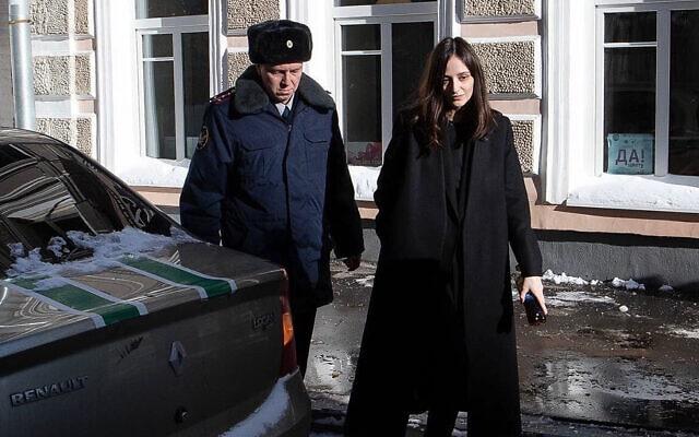 שוטר מלווה את לוסי שטיין ממעצר הבית שבו היא נתונה לבית המשפט, 15 בפברואר 2021 (צילום: באדיבות לוסי שטיין)