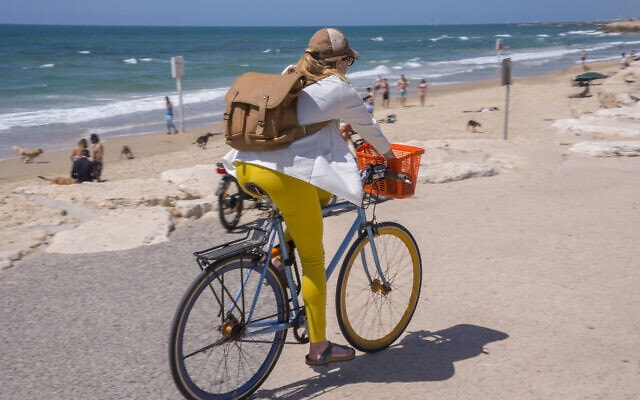 אישה רוכבת על אופניים בטיילת בתל אביב. אילוסטרציה (צילום: iStock)