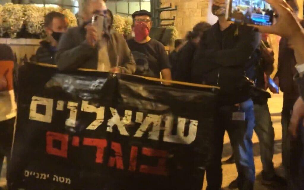 """משה מירון עם השלט """"שמאלנים בוגדים"""" (צילום: צילום מסך מסרטון של ציפי מנשה)"""
