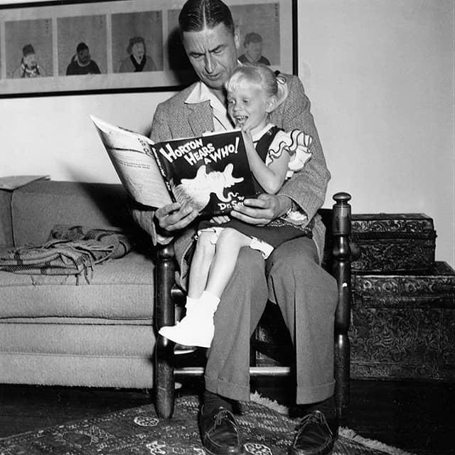 """הסופר והמאייר תאודור סוס גייזל, המוכר כד""""ר סוס, מקריא מספרו לילדה בת ארבע בביתו בקליפורניה, 20 ביוני 1956 (צילום: AP Photo)"""