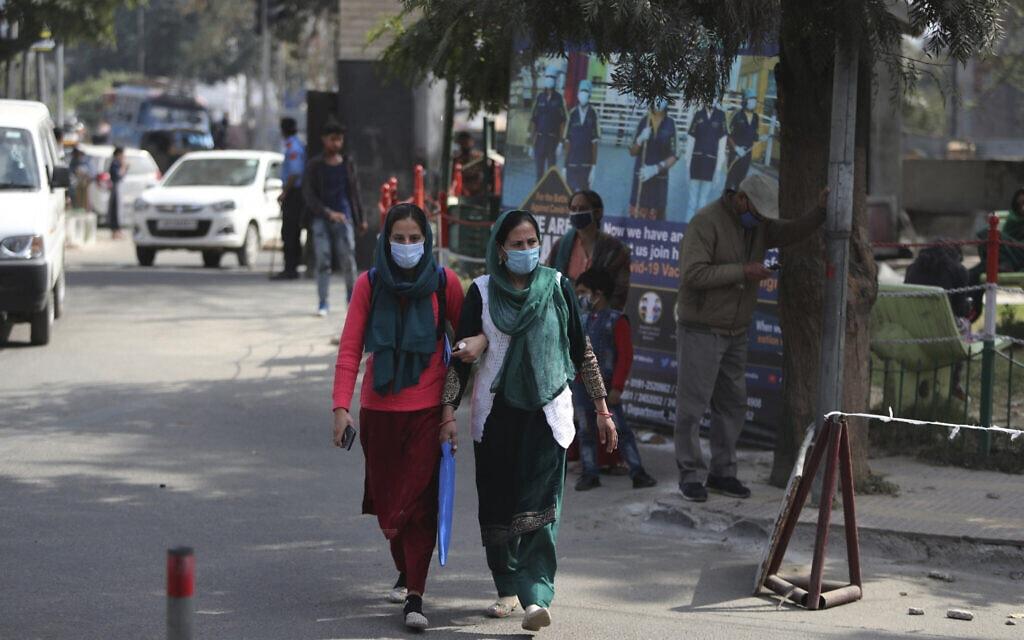 נשים הודיות צועדות ליד בית החולים הממשלתי בג'אמו, הודו. 24 בפברואר 2021 (צילום: AP Photo/Channi Anand)