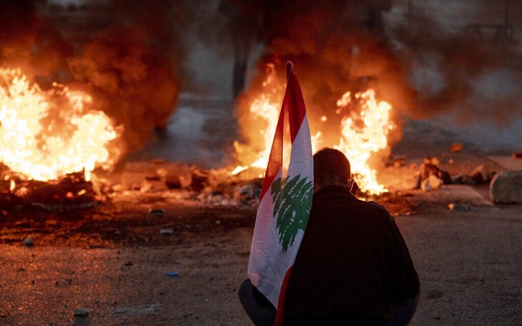 מפגין הנושא את דגל לבנון בביירות, 3 במרץ 2021 (צילום: Hassan Ammar, AP)
