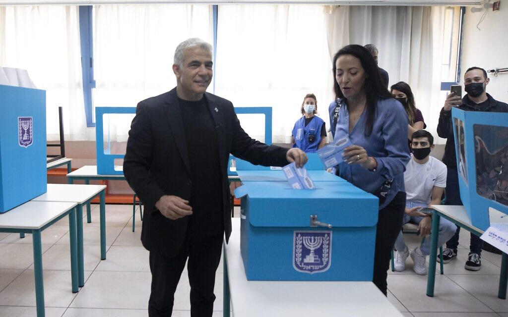 יושב ראש יש עתיד, יאיר לפיד, מצביע בבחירות לכנסת בקלפי בתל אביב לצד אשתו ליהיא, 23 במרץ 2021 (צילום: Sebastian Scheiner, AP)