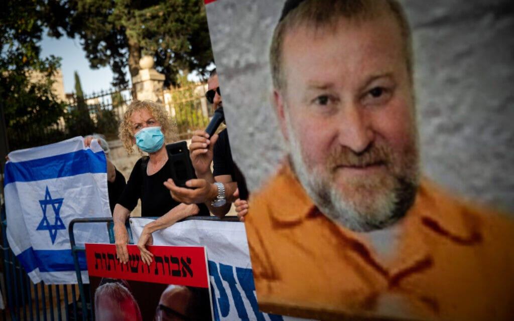 תומכי בנימין נתניהו מפגינים ליד שלט עם עיבוד תמונה של אביחי מנדלבליט, מאי 2020 (צילום: Yonatan Sindel/Flash90)