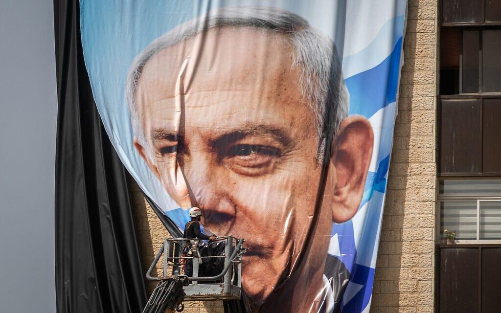 פועלים תולים שלט חוצות ענק של בנימין נתניהו בירושלים, 10 במרץ 2021 (צילום: יונתן זינדל/פלאש90)