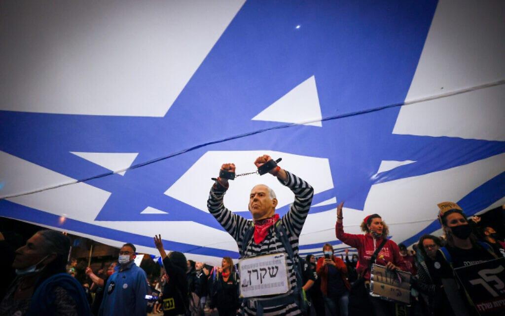 מפגין במסיכת נתניהו ושלט שקרן מתחת לדגל בהפגנה מול בלפור, 20 במרץ 2021 (צילום: Yonatan Sindel/Flash90)