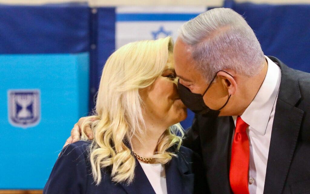 ראש הממשלה בנימין נתניהו ורעייתו שרה מתנשקים בקלפי בבחירות הרביעיות, 23 במרץ 2021 (צילום: Marc Israel Sellem/POOL)