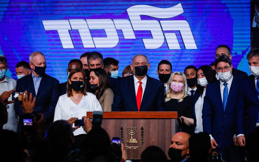 בנימין ושרה נתניהו מוקפים בבכירי הליכוד בליל הבחירות במטה המפלגה,23 במרץ 2021 (צילום: אוליבייה פיטוסי/פלאש90)