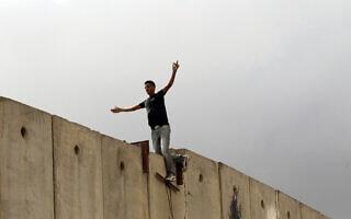 פלסטיני עומד על גדר ההפרדה ליד מחסום קלנדיה, בין רמאללה וירושלים. 23 בספטמבר 2011 (צילום: נתי שוחט/פלאש90)