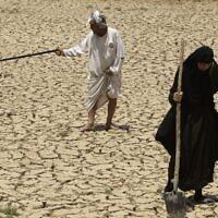 בעל ואישה בודקים את אדמותיהם הצחיחות בגלל הבצורת דרומית לבגדד, עיראק, ביולי 2009 (צילום: AP Photo/Hadi Mizban)