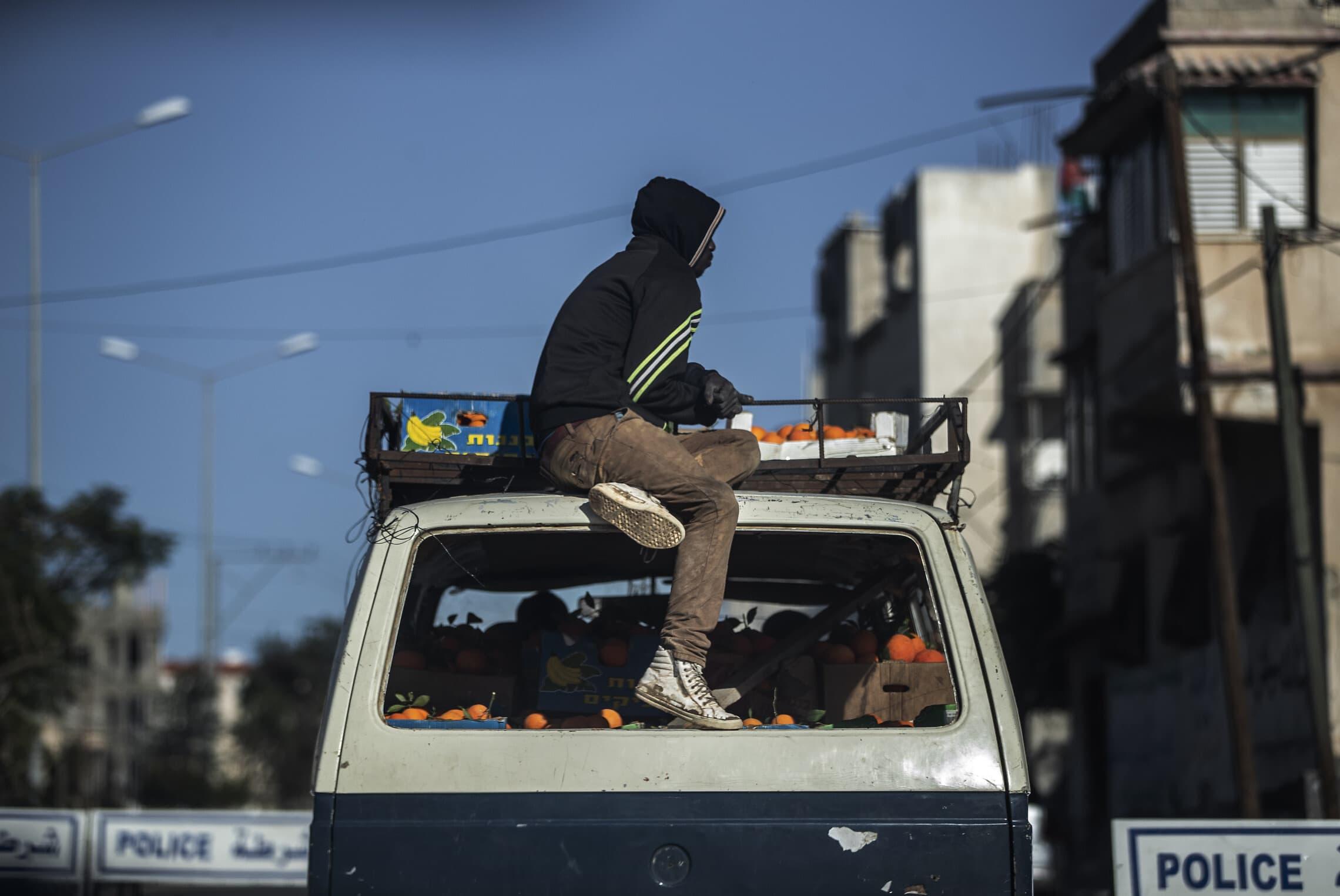 החיים בעזה: צעיר יושב על רכב עם ארגזי תפוזים, פברואר 2021 (צילום: AP Photo/Khalil Hamra)