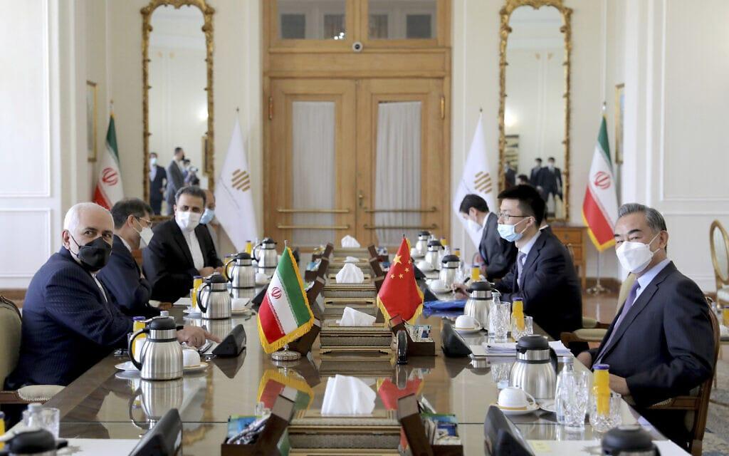שר החוץ של איראן מוחמד ג'וואד זריף (משמאל) ומשלחתו ושר החוץ של סין וואנג יי (מימין) ומשלחתו בפגישה בטהרן לקראת חתימת ההסכם בין שתי המדינות, 27 במרץ 2021 (צילום: AP Photo/Ebrahim Noroozi)