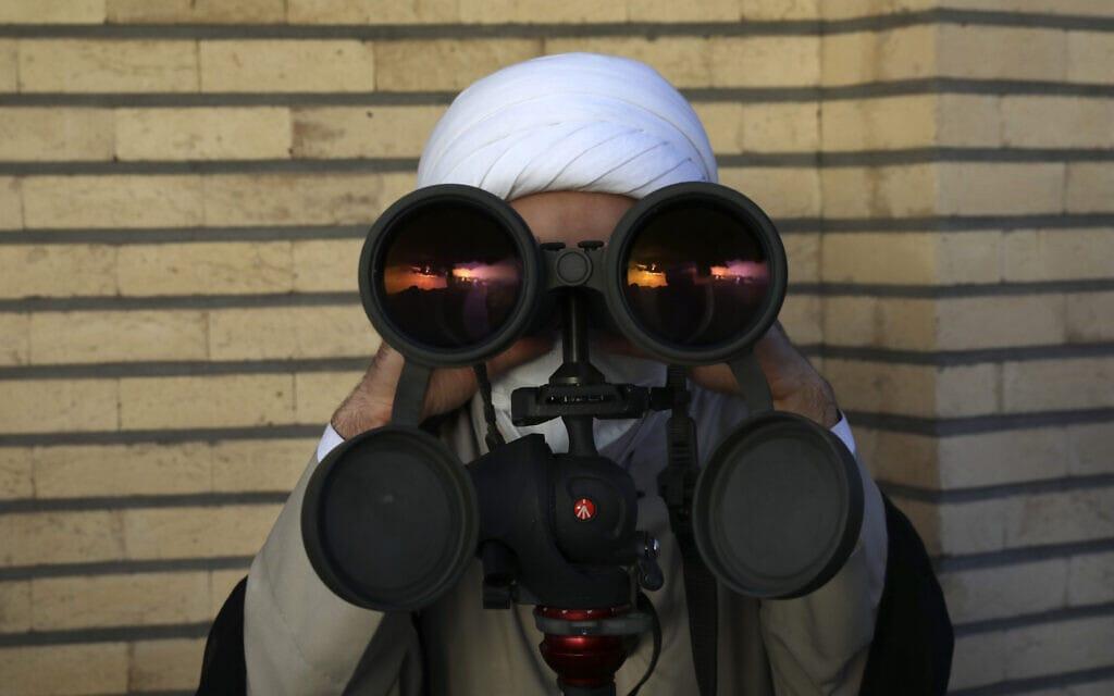 איש דת מוסלמי מביט דרך משקפות בחיפוש אחר הירח החדש, סימן לתחילת חודש הרמדאן. טהרן, איראן, 13 באפריל 2021 (צילום: AP Photo/Vahid Salemi)