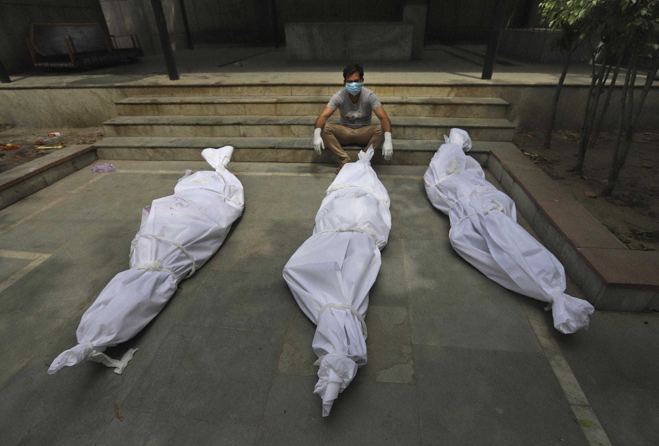 אזרח הודי עם גופות בני משפחתו שמתו מנגיף הקורונה בניו דלהי, הודו, 20 באפריל 2021 (צילום: AP Photo)