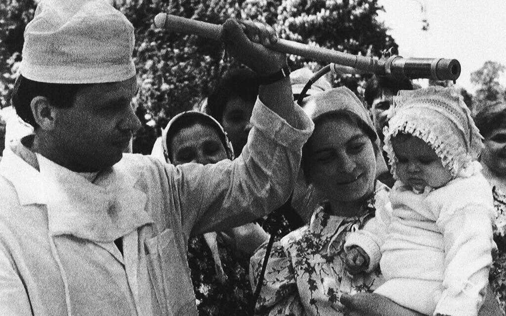טכנאי רפואה סובייטי בודק ילד שפונה מאזור התאונה הגרעינית בצ'רנוביל, 11 במאי 1986 (צילום: Boris Yurchenko, AP)