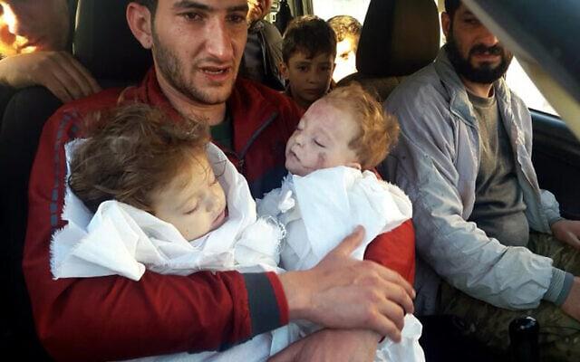 אב אוחז בגופות ילדיו התאומים, שנהרגו במתקפה הכימית בח'אן שייח'ון שבסוריה, 4 באפריל 2017 (צילום: Alaa Alyousef via AP, File)