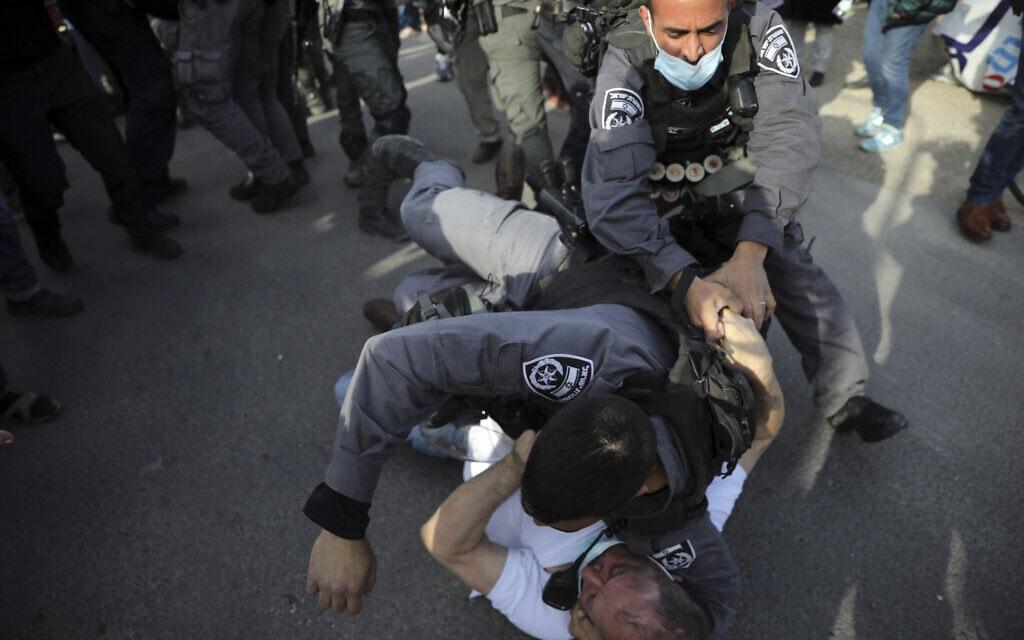 """חבר הכנסת עופר כסיף (בחולצה לבנה) על הקרקע, כשמעליו שוטרי יס""""מ, בהפגנה במזרח ירושלים, 9 באפריל 2021 (צילום: Mahmoud Illean, AP)"""