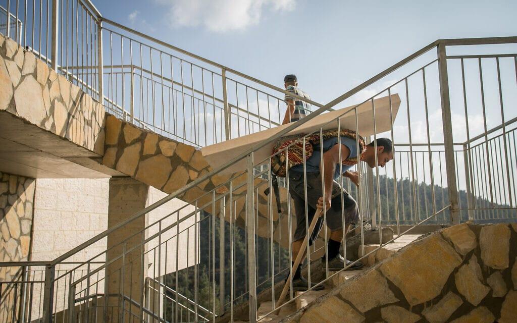 עובד חברה קדישא סוחב מצבה לקבר טרי בהר המנוחות בירושלים – בית עלמין נטול נגישות במרבית החלקות בו (צילום: יונתן זינדל/פלאש90)