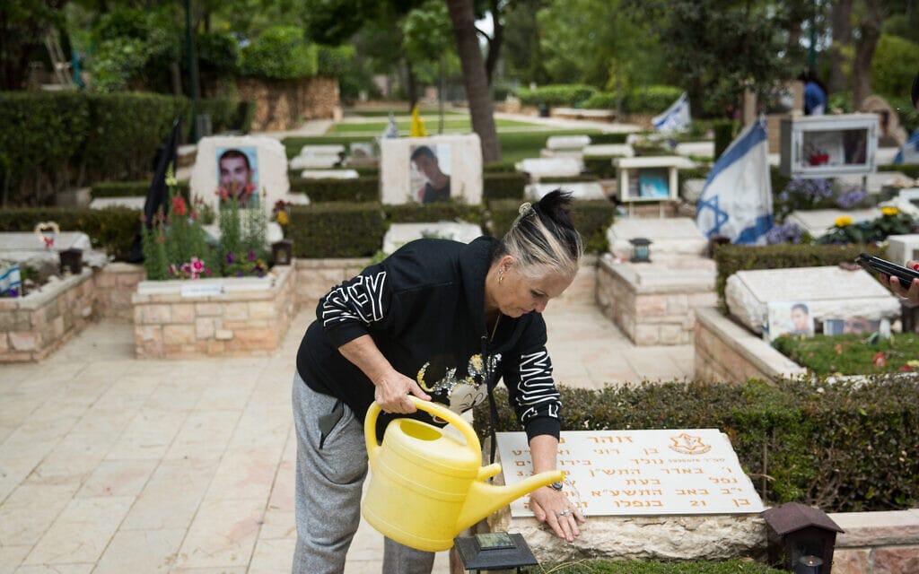 אם שכולה מנקה את קבר בנה בבית העלמין הצבאי בהר הרצל (צילום: יונתן זינדל/פלאש90)