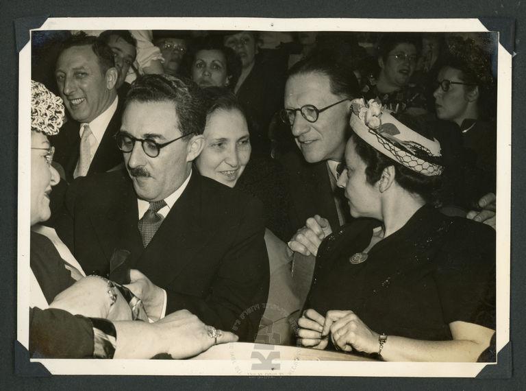 """משה שרת (משמאל) ורעייתו ציפורה (מאחוריו) חותם למעריצים בביקור בארגון ה""""בונים"""", ניו-יורק, ארצות הברית, יוני 1948 (צילום: אלבום יעל מדיני-שרת, יד בן-צבי)"""