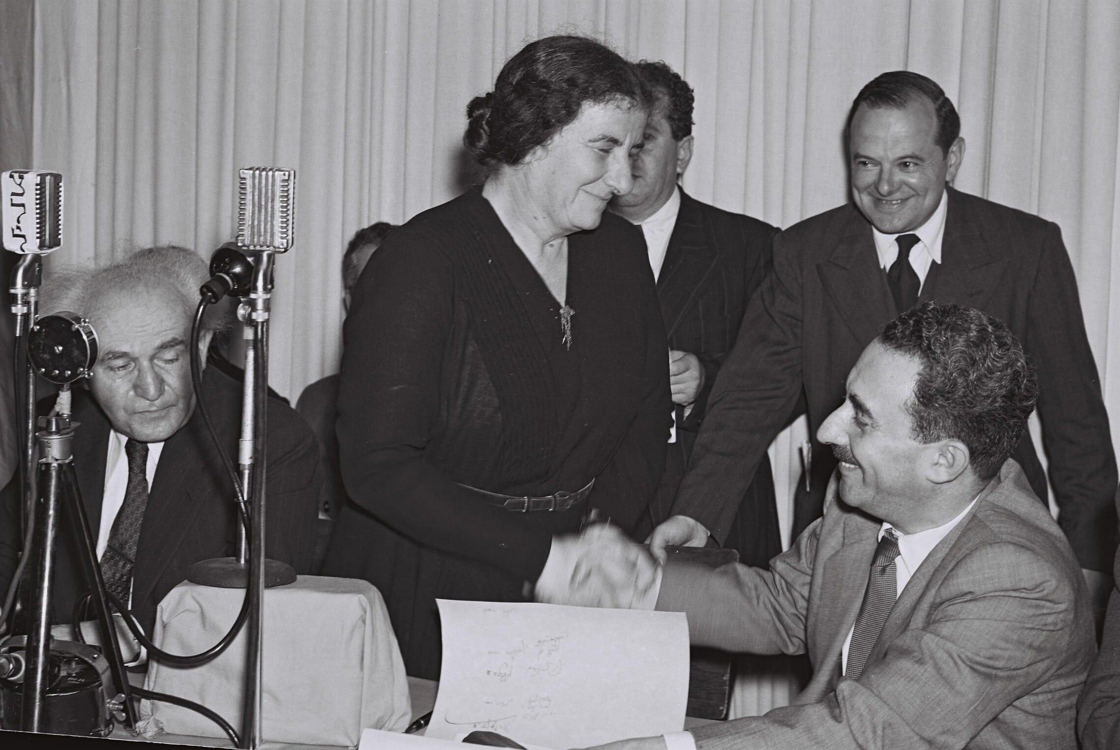 """גולדה מאיר לוחצת את ידו של משה שרת אחרי הכרזת המדינה. משמאל, דוד בן-גוריון, 14 במאי 1948 (צילום: פרנק שרשל/לע""""מ)"""