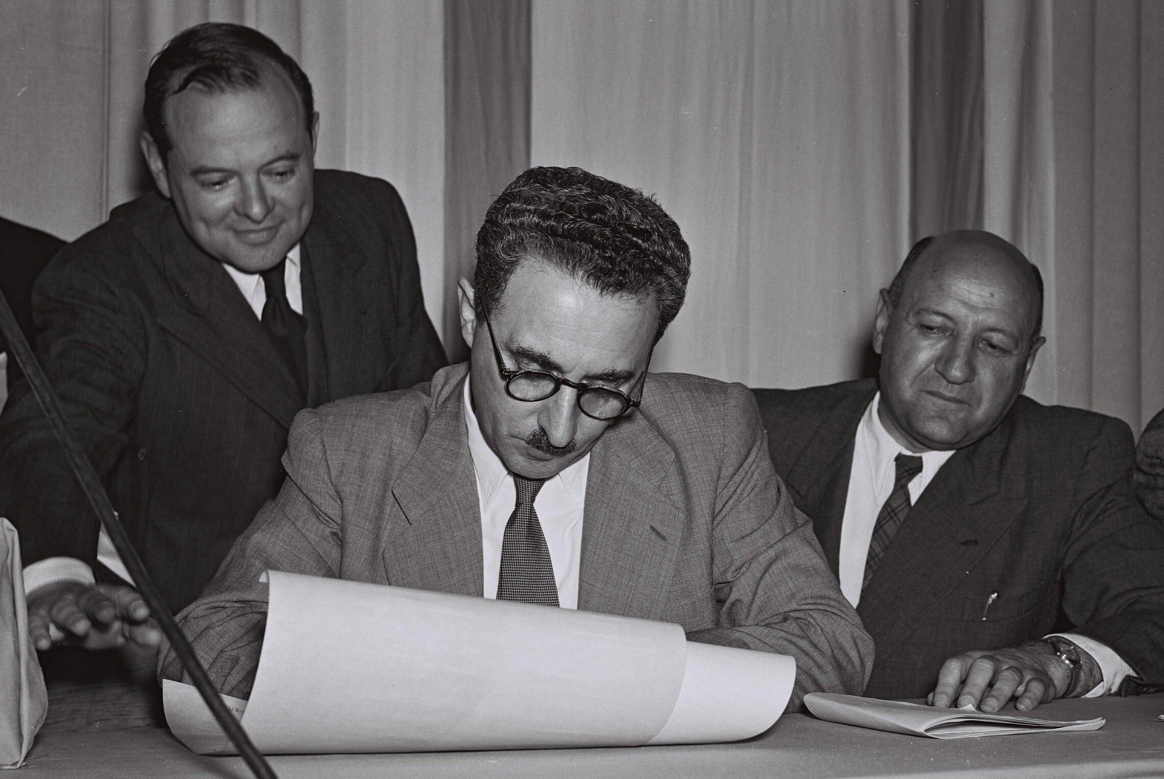 """משה שרת חותם על מגילת עצמאות ישראל, 14 במאי 1948 (צילום: פרנק שרשל/לע""""מ)"""