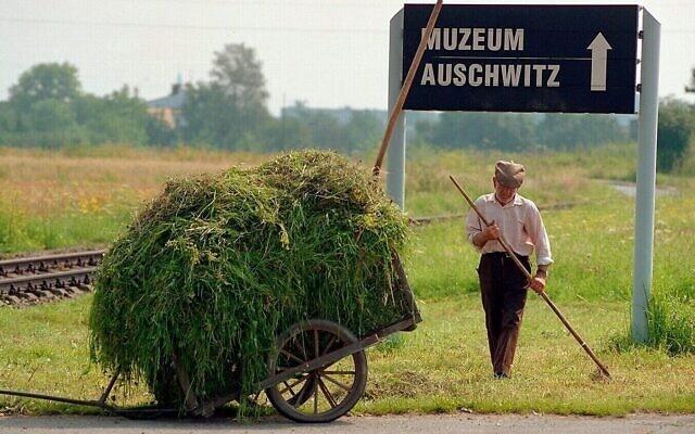 """פועל עובד ליד פסי הרכבת שהובילו לאושוויץ. צילום מהסרט התיעודי """"הימים האחרונים"""" שצולם ב-1998"""