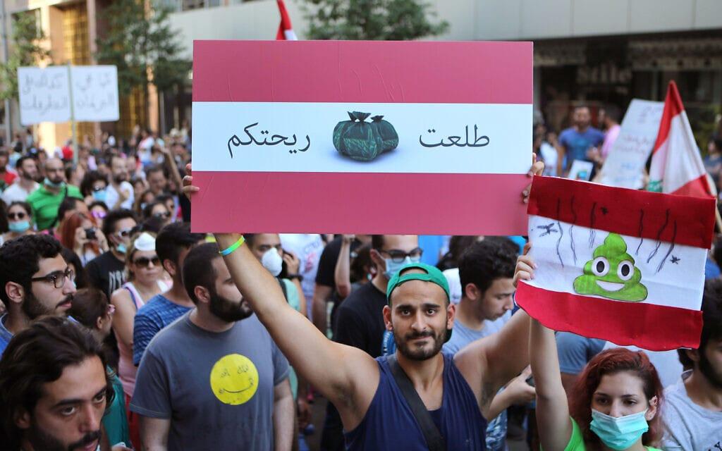 """מפגינים לבנונים נגד משבר האשפה והשחיתות השלטונית עם השלטים """"אתם מסריחים"""", בירות 2015 (צילום: AP Photo/Hussein Malla)"""