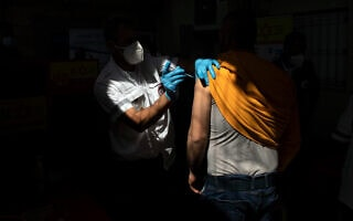 פועל פלסטיני מקבל חיסון נגד קורונה של חברת מודרנה במעבר טרקומייה בגדה המערבית, 8 במרץ 2021 (צילום: AP Photo/Sebastian Scheiner)