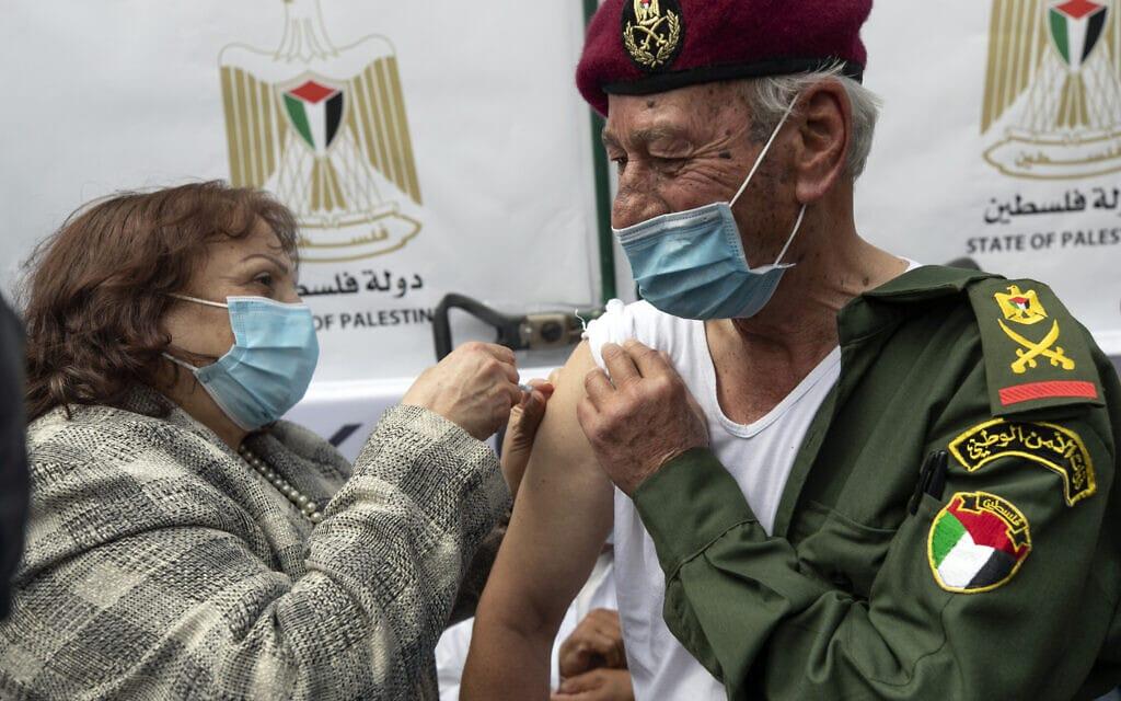 קצין בדימוס של הרשות הפלסטינית מקבל חיסון נגד קורונה ברמאללה, 21 במרץ 2021 (צילום: AP Photo/Nasser Nasser)