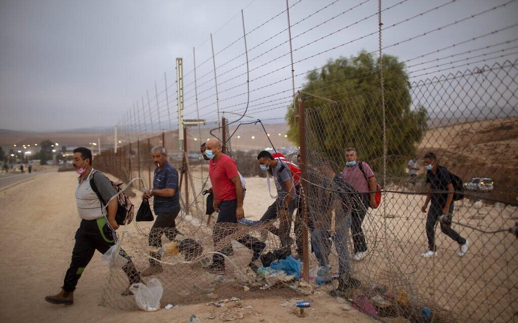 עובדים מהרשות הפלסטינית עוברים דרך פרצה בגדר ליד חברון, 6 בספטמבר 2020 (צילום: AP Photo/Oded Balilty)
