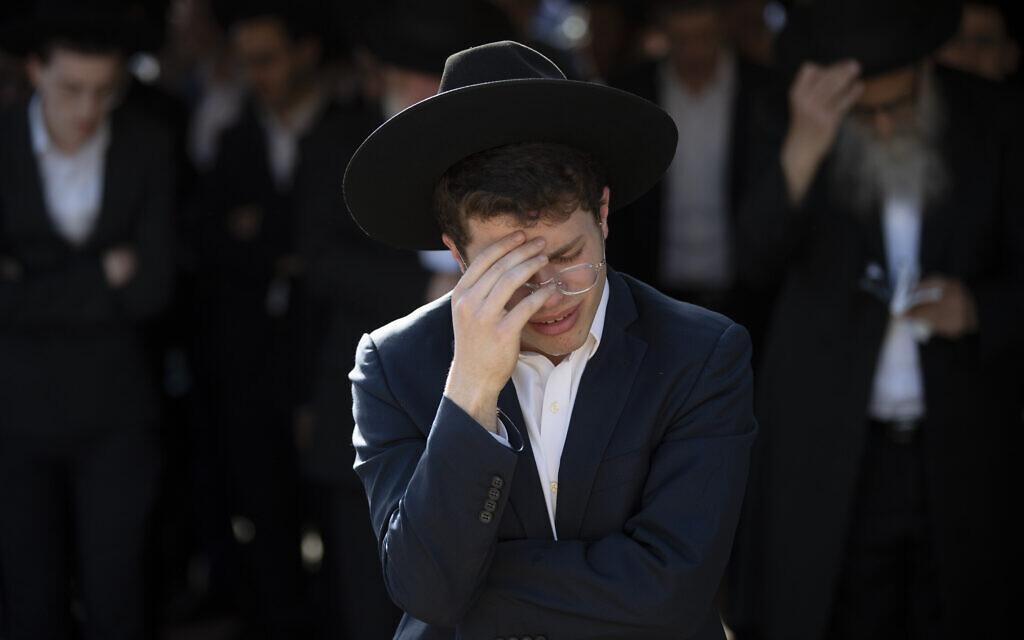 """צעיר חרדי מתאבל בהלוויתו של משה בן שלום, שנהרג באסון ל""""ג בעומר בהר מירון, 30 באפריל 2021 (צילום: AP Photo/Oded Balilty)"""