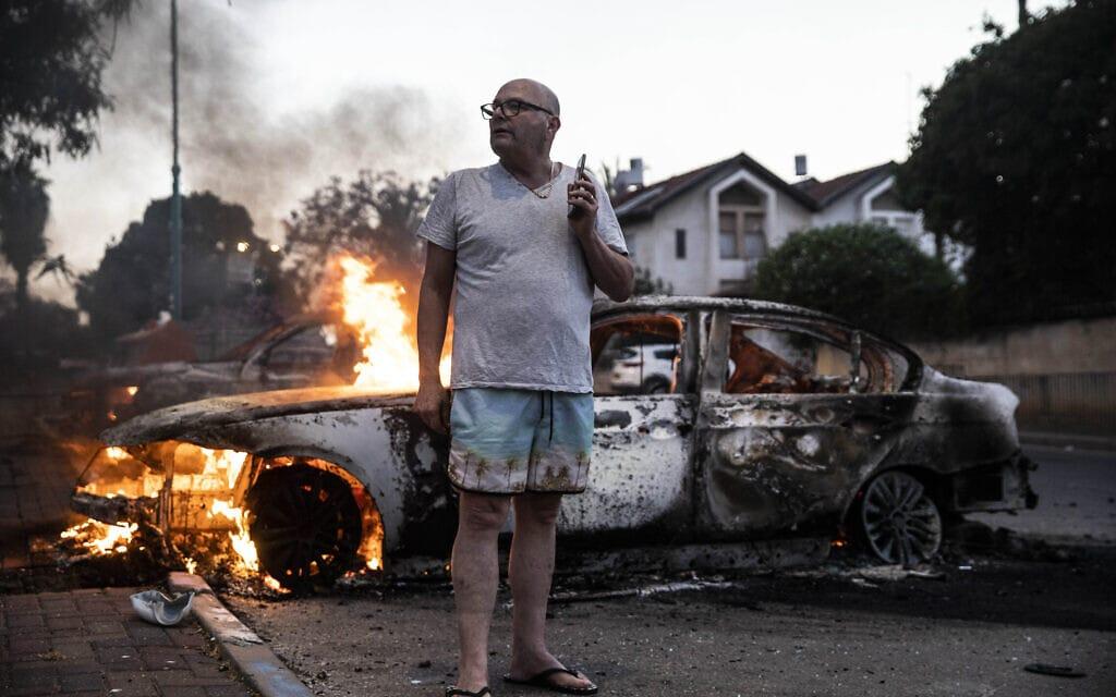 יעקב סימונה ליד מכוניתו שהוצתה בארועים האלימים בלוד, 11 במאי 2021 (צילום: AP Photo/Heidi Levine)