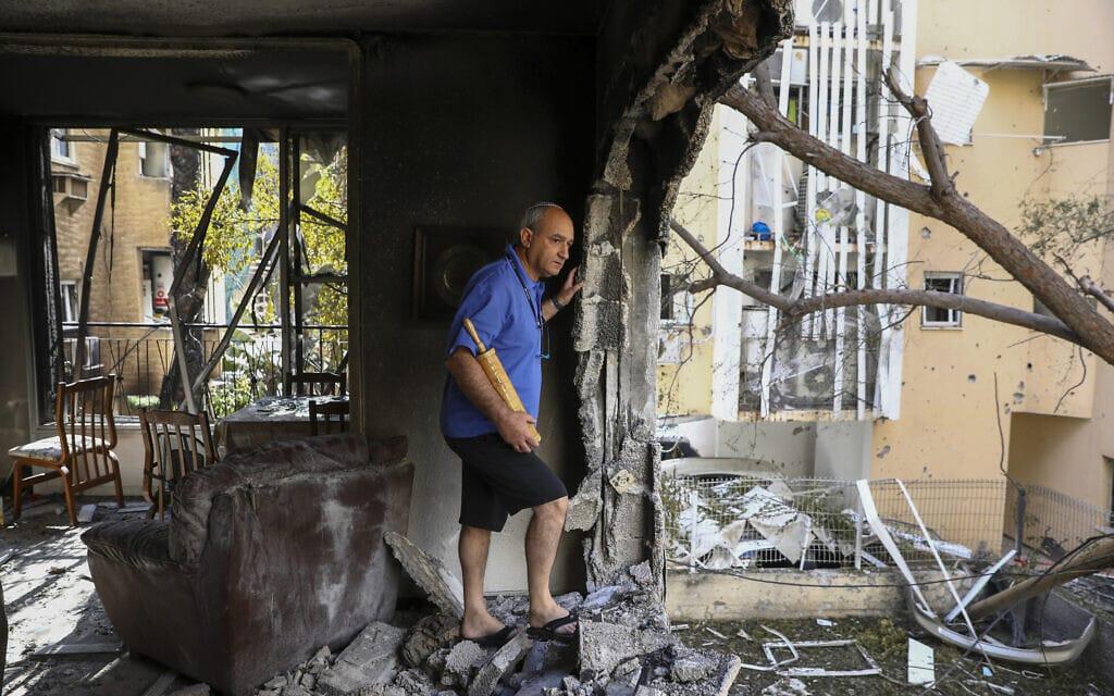תושב פתח תקווה בביתו שנפגע בפגיעה ישירה מרקטה שנורתה מעזה, 13 במאי 2021 (צילום: AP Photo/Oded Balilty)