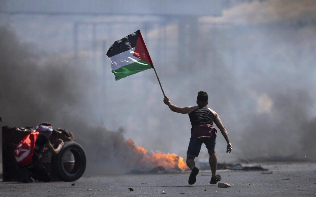 """מפגין פלסטיני מנופף בדגל פלסטין בהתנגשויות עם כוחות צה""""ל ליד מעבר הגבול חווארה בגדה המערבית, 14 במאי 2021 (צילום: AP Photo/Majdi Mohammed)"""