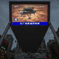 מסך בקניון בבייג'ין משדר דיווח על טיאנוון-1 – משימת החלל למאדים, 15 במאי 2021 (צילום: Mark Schiefelbein, AP)