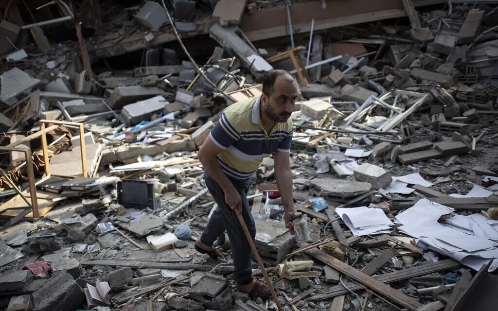 """פלסטיני בין הריסות של מבנה שהפציץ צה""""ל בעיר עזה, 18 במאי 2021 (צילום: Khalil Hamra, AP)"""