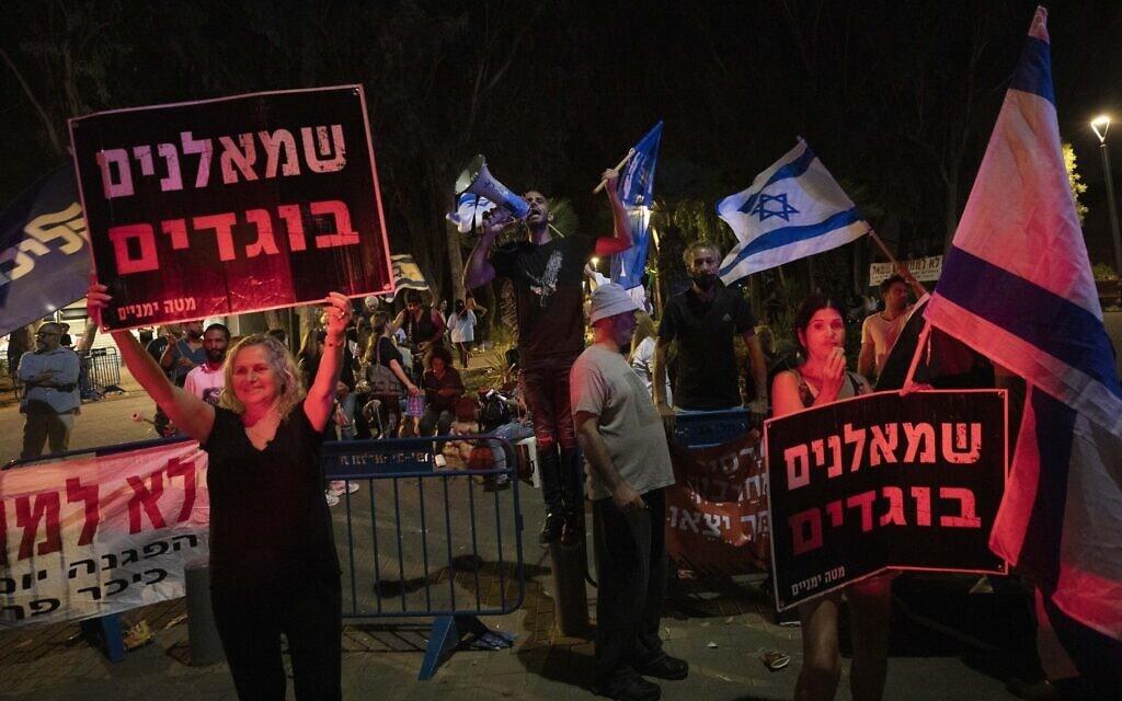 """מפגינים מחזיקים בשלטים """"שמאלנים בוגדים"""" בהפגנה מתחת לביתה של איילת שקד, 30 במאי 2021 (צילום: AP Photo/Sebastian Scheiner)"""