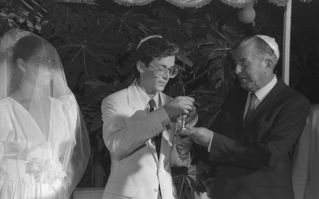 """הנשיא חיים הרצוג מתחת לחופת בנו, יצחק (בוז'י), בנישואי למיכל, 14 באוגוסט 1985 (צילום: יעקב סער/לע""""מ)"""