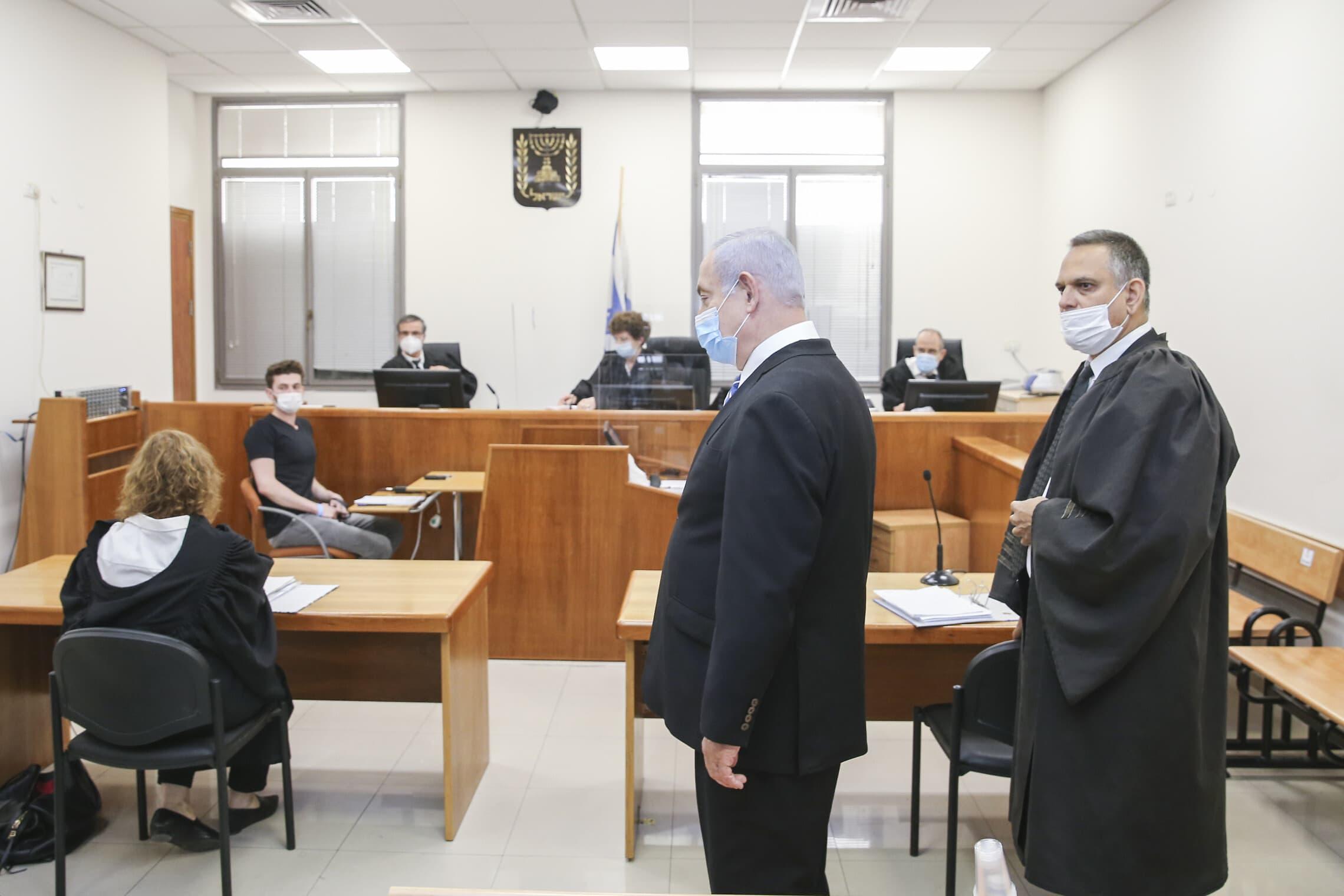 """עו""""ד מיכה פכטמן ובנימין נתניהו עומדים, התובעת ליאת בן-ארי (משמאל) יושבת מול השופטים ברגע פתיחת משפטו של ראש הממשלה בבית המשפט המחוזי בירושלים, 24 במאי 2020 (צילום: Amit Shabi/POOL)"""