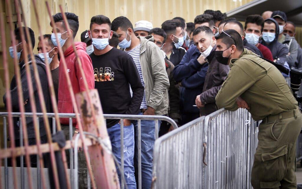 פלסטינים העובדים באזור התעשייה ברקן עומדים בתור לקבל את החיסון נגד קורונה מישראל בגדה המערבית, 11 באפריל 2021 (צילום: Nasser Ishtayeh/Flash90)