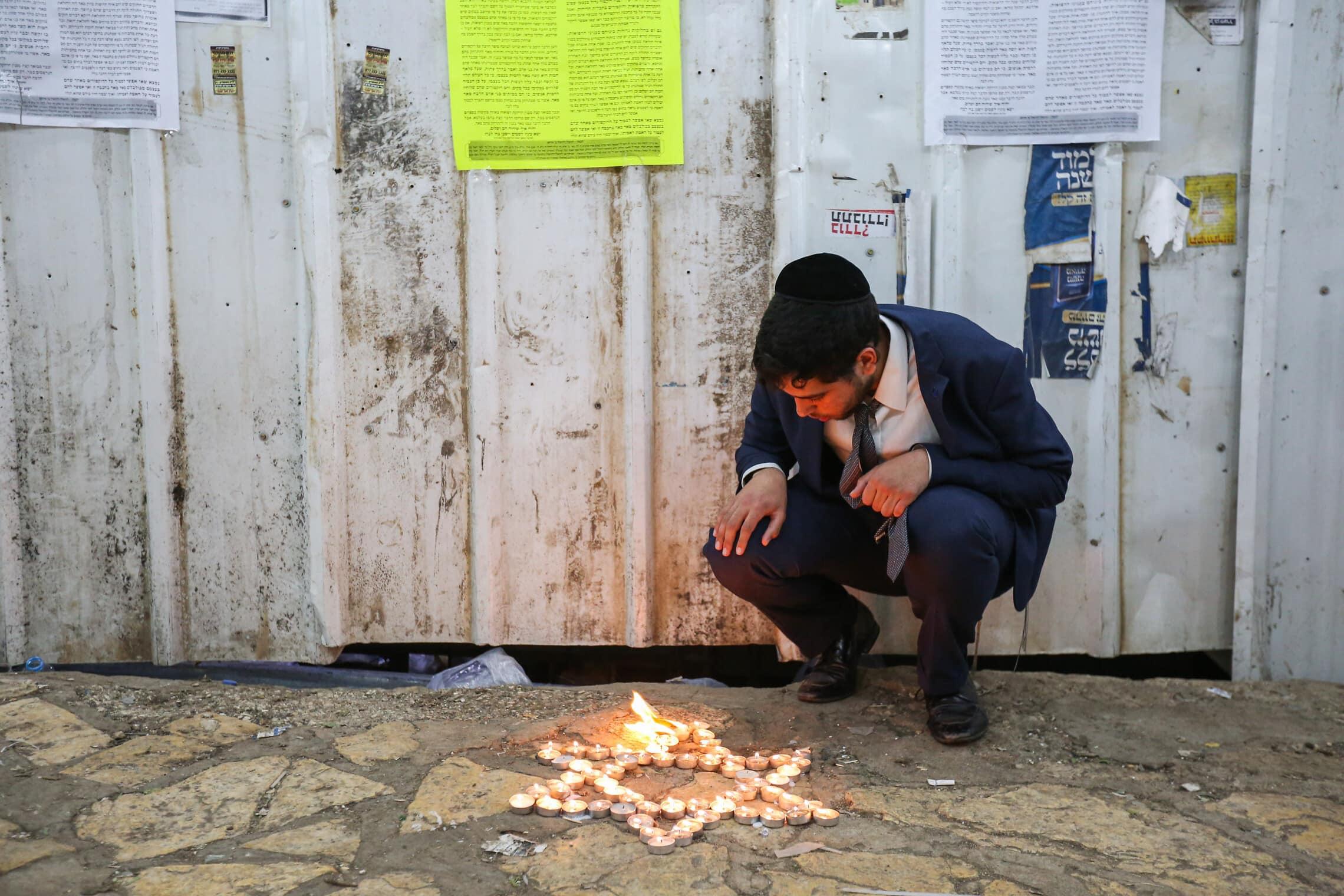 חרדי מדליק נרות בזירת הארוע של האסון בהר מירוון, 1 במאי 2021 (צילום: דוד כהן/פלאש90)