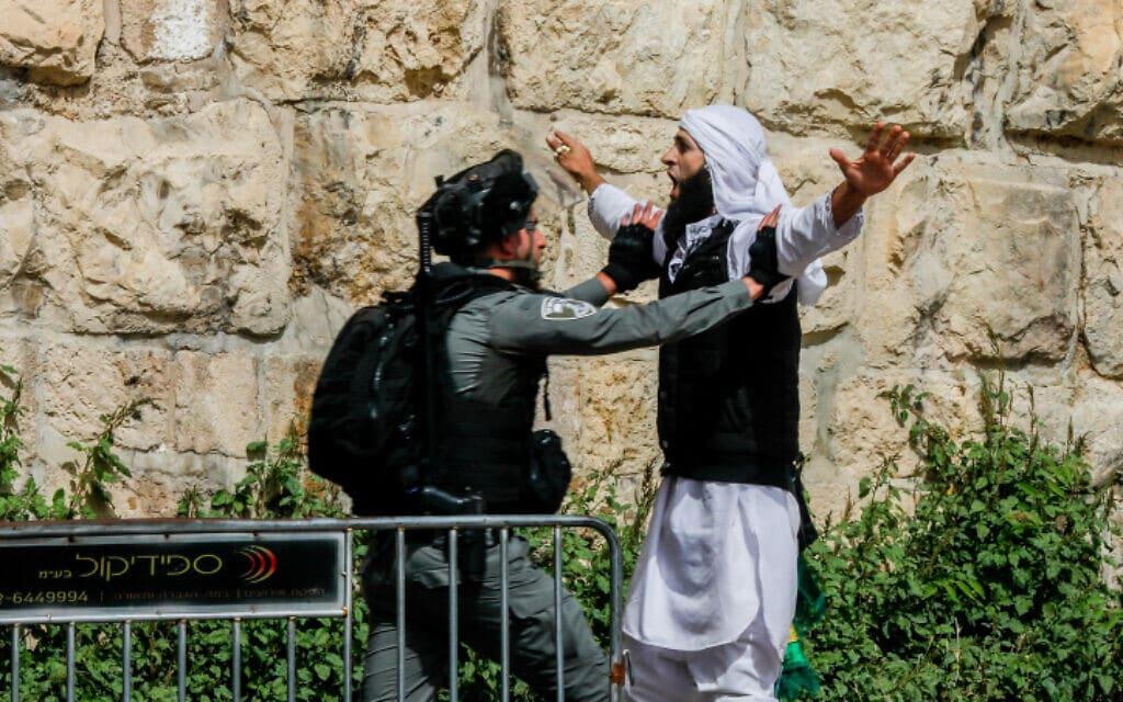שוטר מג״ב עוצר מפגין לאחר שיהודי התנגש בחומה והותקף בירושלים, 10.5.21 (צילום: Olivier Fitoussi/Flash90)