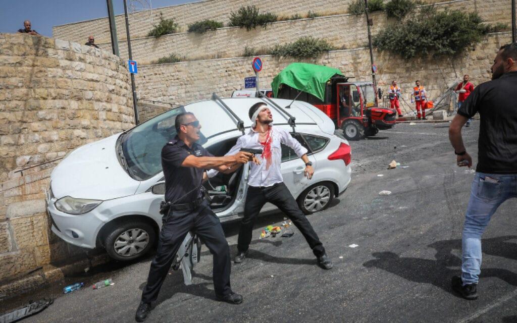 שוטר ישראלי מכוון את נשקו לעבר ערבים שניסו לפגוע ביהודי לאחר שסטה מהדרך והתנגש בחומהף ביום ירושלים, 10.5.21 (צילום: Olivier Fitoussi/Flash90)