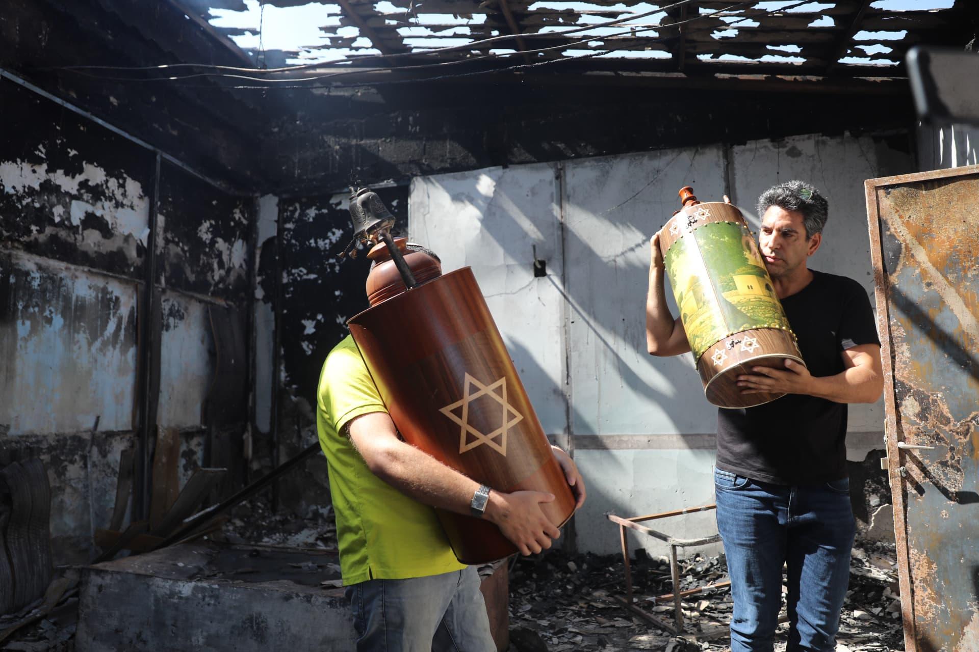 יהודים מוציאים ספרי תורה מפוייחים מבית כנסת שהוצת בלוד על ידי ערבים, ב-12 במאי 2021 (צילום: יונתן זינדל/פלאש90)