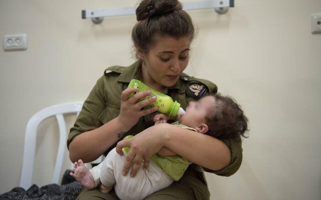 """חיילת צה""""ל מאכילה תינוק מסוריה ב-2017 (צילום: דובר צה""""ל)"""