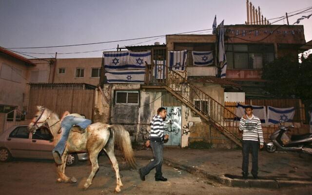 פלסטיני עומד מחוץ לבית עם תושבים יהודים בשכונת שייח' ג'ראח ב-2009 (צילום: AP Photo/Dan Balilty)