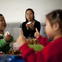 שני ילדים סינים יחד עם אימם (צילום: AP Photo/Alexander F. Yuan)