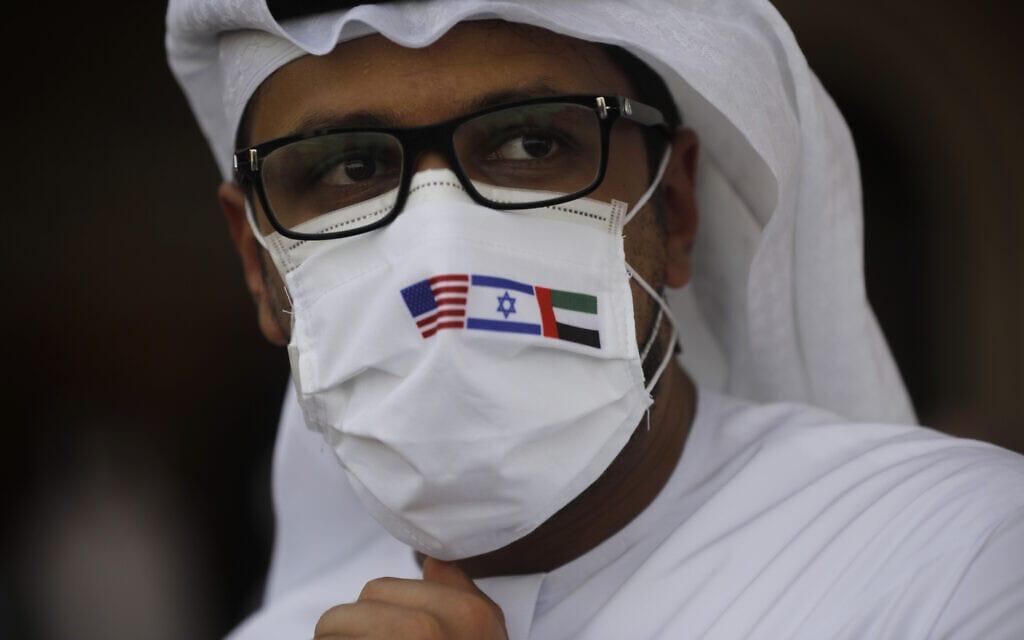 """תושב איחוד האמירויות באבו דאבי עוטה מסכה שעליה דגלי האיחוד, ישראל וארה""""ב, בטקס נחיתת טיסת אל על הראשונה מישראל, ב-31 באוגוסט 2021 (צילום: Nir Elias/Pool Photo via AP)"""
